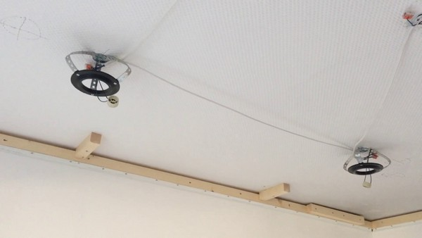 На фото: в центре потолка - закладные под точечные светильники и проводка к ним. По периметру потолочный багет для тканевых потолков смонтированный через деревянный брус.